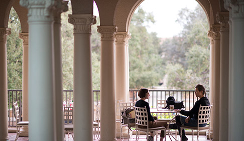 Two figures sit on the Branca patio at JSC framed by columns on either side
