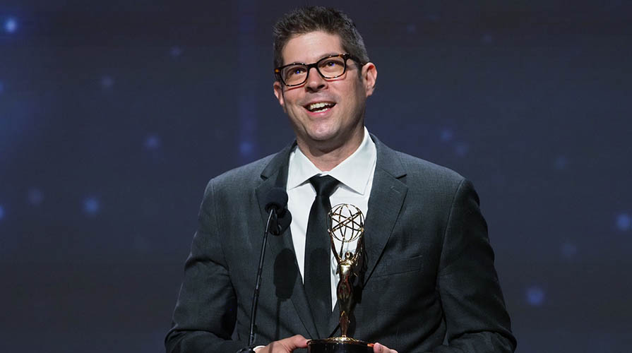 Professor Adam Schoenberg holds his Emmy award