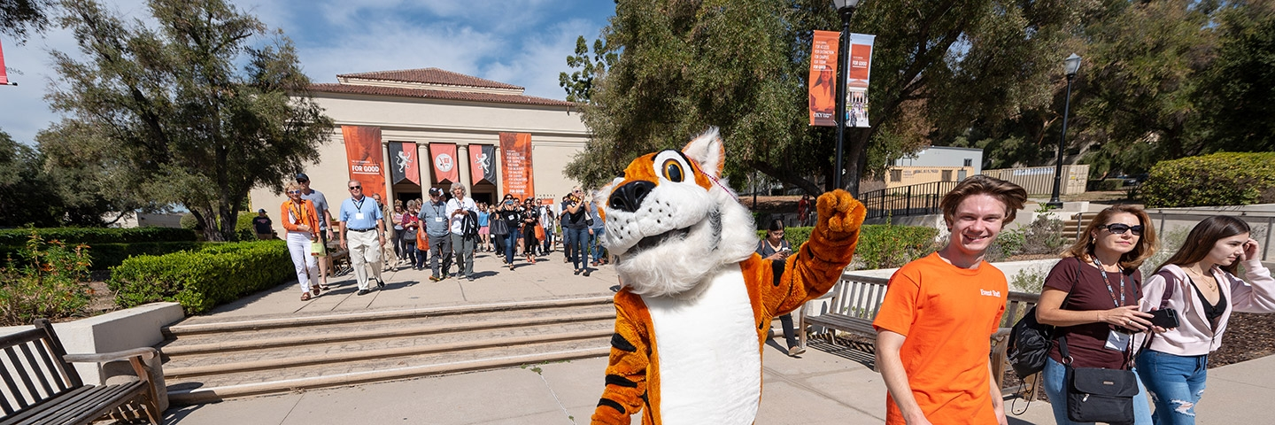 Oswald the Tiger strolls in front of Thorne Hall with students, alumni, and families