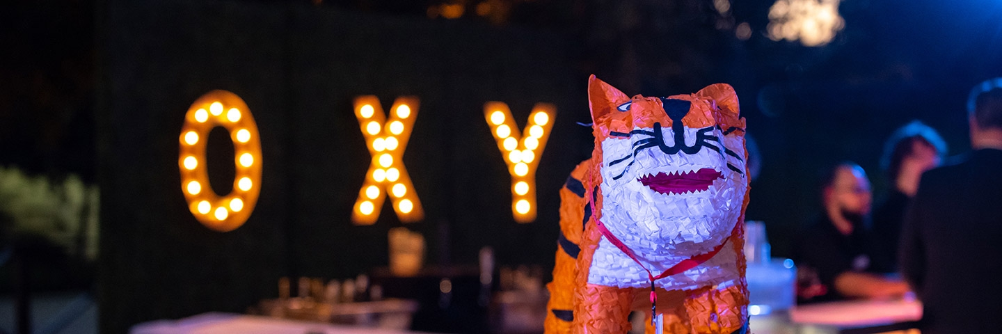 "An Oswald the Tiger pinata in front of a sign made of light bulbs that reads ""Oxy"""